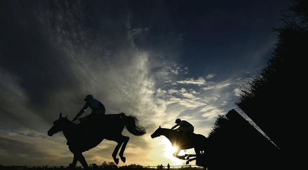 A silhouette of horses jumping the last fence during a hurdle race at Huntingdon yesterday