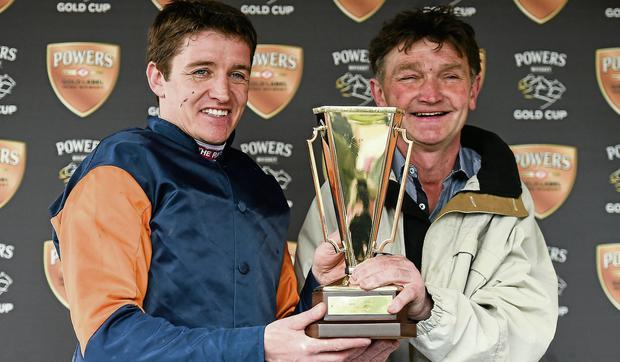 Jockey Barry Geraghty and trainer Michael Winters lift the Gold Cup after Rebel Fitz's victory at Fairyhouse yesterday.