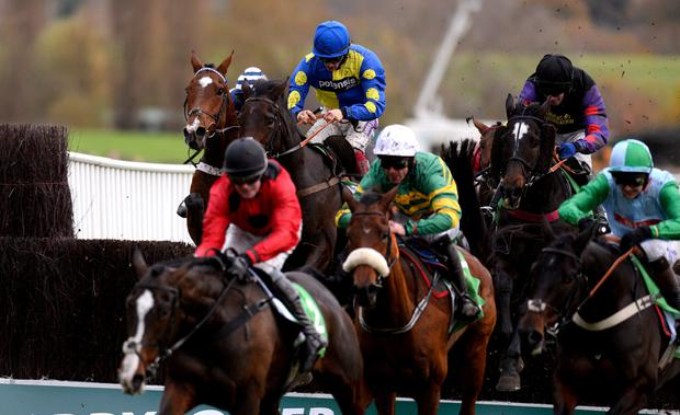 Sam Twiston-Davies riding Caid Du Berlais (L, blue/yellow) clear the last to win The Paddy Power Gold Cup Steeple Chase at Cheltenham