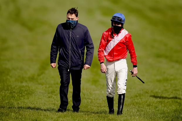 Jockey Jack Kennedy is met by trainer Henry de Bromhead after falling from Envoi Allen during The Marsh Novices' Chase during day three of the Cheltenham Festival. Photo: Alan Crowhurst/PA Wire.