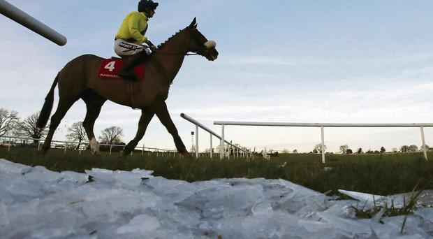 Luska Lad ridden by Danny Mullins passes by ice that was cleared from the track on the way to post in The Punchestown Rated Hurdle