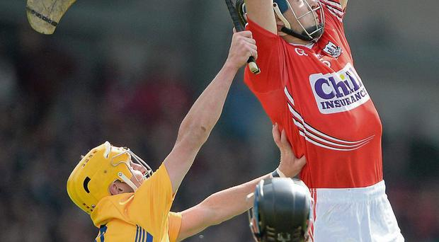 Christopher Joyce of Cork soars hightest to field dropping ball ahead of Clare's Colm Galvin during the Munster SHC semi-final showdown in Limerick