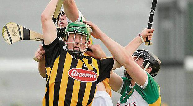 Kilkenny's Richie Reid jumps with Offaly duo Owen McGrath and Sean Dolan