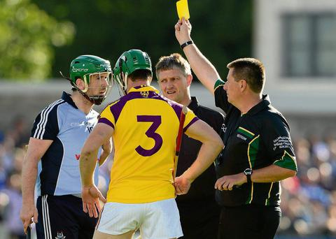 Referee Brian Gavin, right linesman Barry Kelly by his side issues a yellow card to Wexford's Tomas Waters