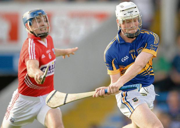 Bill Walsh shoots to score Tipperary's first goal despite the attention of Cork's Christopher Joyce during last night's Munster U21 HC semi-final in Thurles