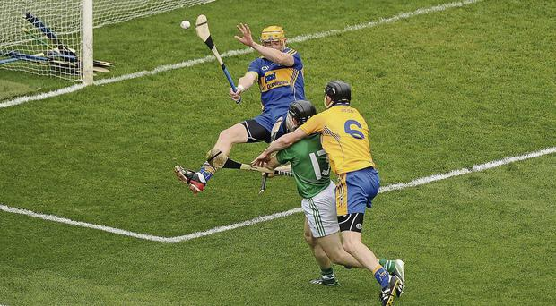 Clare players Pádraic Collins, left, and Darach Honan celebrate after the sliotar is bundled into the Limerick net during the first half
