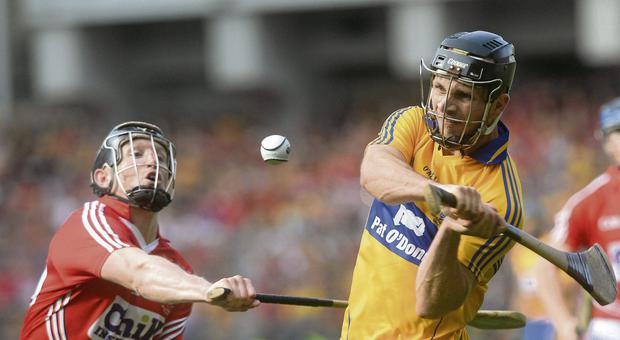 Clare's Domhnall O'Donovan shoots to score the equalising point in the All-Ireland final despite the attentions of Cork's Stephen White