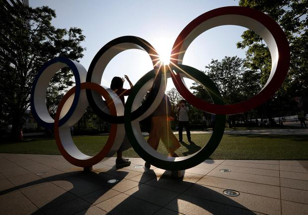 Visitors try to take photos in front of the Olympic Rings monument outside the Japan Olympic Committee headquarters near the National Stadium in Tokyo. Photo: Reuters/Issei Kato