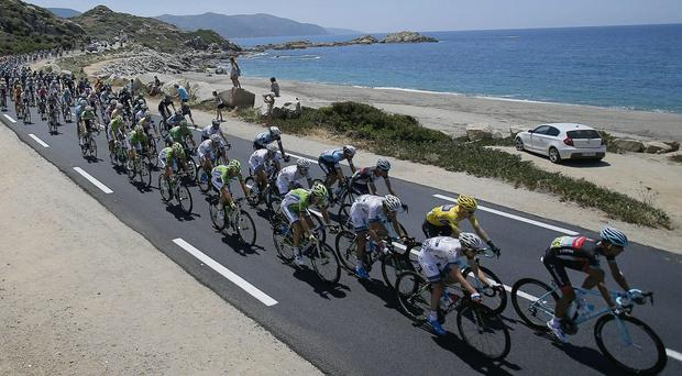 The packs with Jan Bakelants of Belgium, wearing the overall leader's yellow jersey, rides along the Mediterranean Sea near Calcatoggio during the third stage of the Tour de France cycling race over 145.5 kilometers (91 miles) with start in Ajaccio and finish in Calvi, Corsica island, France, Monday July 1, 2013. (AP Photo/Christophe Ena)