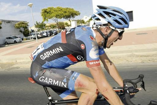 Dan Martin grimaces in pain as he remounts his bike after a nasty fall in yesterday's stage of the Vuelta a Espana