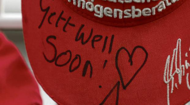 A cap is left by a fan with a birthday wish for Michael Schumacher and (below) Phil Quinlan with his wife Helena
