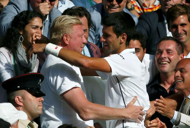 Novak Djokovic of Serbia (C) celebrates with his coach Boris Becker after defeating Roger Federer of Switzerland in their men's singles final tennis match at the Wimbledon Tennis Championships