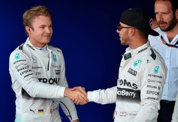 Mercedes AMG Petronas F1 Team's British driver Lewis Hamilton (R) shakes hands with Mercedes AMG Petronas F1 Team's German driver Nico Rosberg after the qualifying session at the Silverstone circuit in Silverstone on July 4, 2015 ahead of the British Formula One Grand Prix. Hamilton took pole ahead of teammate Rosberg with Massa in third place. AFP PHOTO / ANDREJ ISAKOVICANDREJ ISAKOVIC/AFP/Getty Images