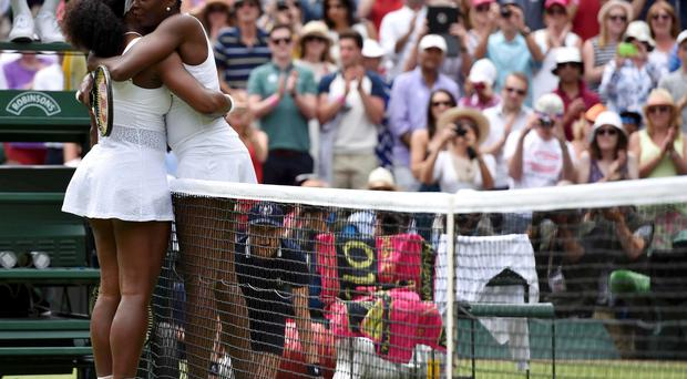 Serena and Venus Williams embrace in front of a standing ovation at Centre Court yesterday
