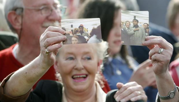 A woman in the crowd holds up a picture of Ali Photo: Niall Carson/PA Wire