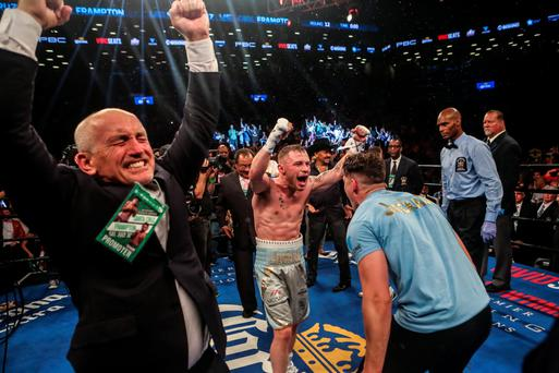 Carl Frampton turns to his trainer Shane McGuigan as Barry McGuigan, left, leads the celebrations Picture: Getty