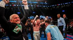 Carl Frampton turns to his trainer Shane McGuigan as Barry McGuigan, left, leads the celebrations after a huge world title win New York last year Picture: Getty