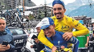 Julian Alaphilippe, wearing the leader's yellow jersey, is carried on the back of his teammate Enric Mas after yesterday's stage was cut short. Photo: Getty Images