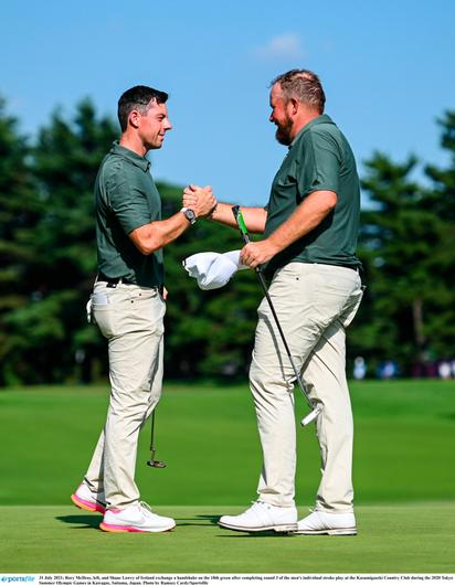 Rory McIlroy, left, and Shane Lowry of Ireland exchange a handshake on the 18th green after completing round 3