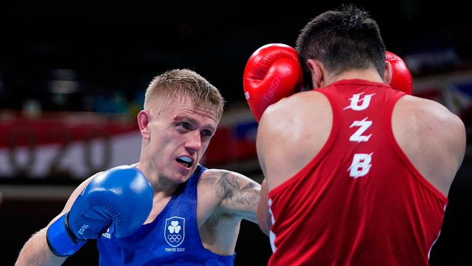 Mirazizbek Mirzakhalilov (red) of Uzbekistan exchanges punches with Kurt Walker of Ireland on day five of the Tokyo 2020 Olympic Games. (Photo by Frank Franklin - Pool/Getty Images)