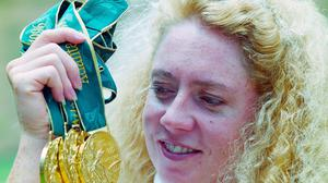 Michelle Smith poses with her three gold medals after the Atlanta Olympic Games of 1996. Photo: Billy Stickland