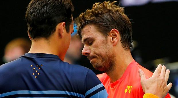 Milos Raonic consoles Stan Wawrinka after winning their fourth round match at the Australian Open