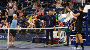 Kevin Anderson of South Africa and Diego Schwartzman of Argentina discuss the wet court with the umpire during their men's singles second round match at the US Open Tennis Championship at the Billie Jean King National Tennis Centre. Photo: Getty Images