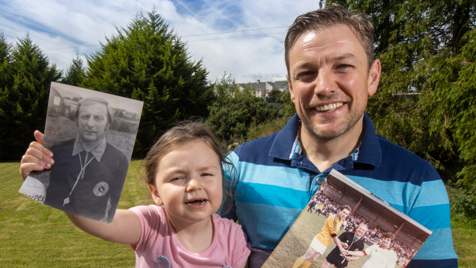 David Price with his daughter Harper (3) holding pictures of his late father, referee Johnny Price. Photo: Mark Condren