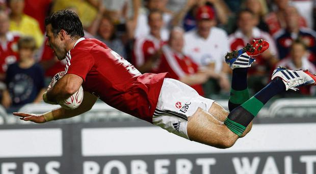 Mike Phillips dives over for a Lions' try against the Barbarians yesterday