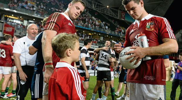 Jonathan Sexton autographs a gaelic football for eight-year-old Odhran Neville as Jamie Heaslip looks on following the Lions' victory over the Barbarians in Hong Kong on Saturday