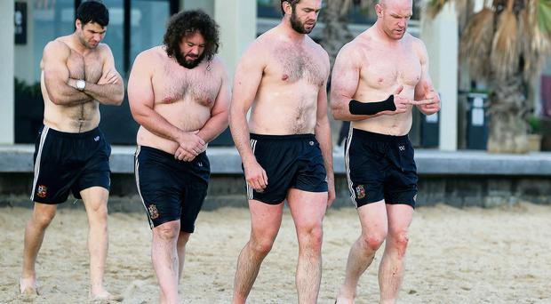 Paul O'Connell discusses his broken arm with Geoff Parling during the Lions recovery session at St Kilda's Beach in Melbourne yesterday – Welsh internationals Mike Phillips (far left) and Adam Jones seem to be feeling the effects of the cold
