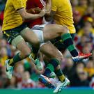 British and Irish Lions' George North is caught between Australia Wallabies' Jesse Mogg and Joseph Tomane