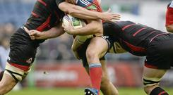 Munster's James Cronin is tackled by Edinburgh duo Grant Gilchrist, left, and David Denton at Murrayfield on Saturday