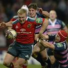 Munster's Keith Earls attempts to get away from Gloucester pair Freddie Burns, left, and Rob Cook