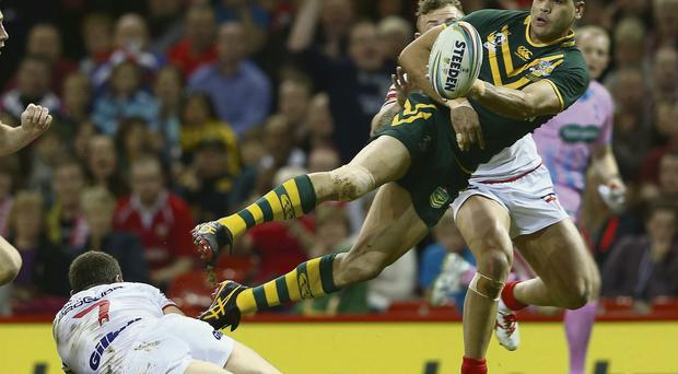 Australia's Greg Inglis passes to set up Jonathan Thurston (not pictured) to score their side's first try against England during the opening Rugby League World Cup game at the Millennium Stadium on Saturday. Australia won the match 28-20
