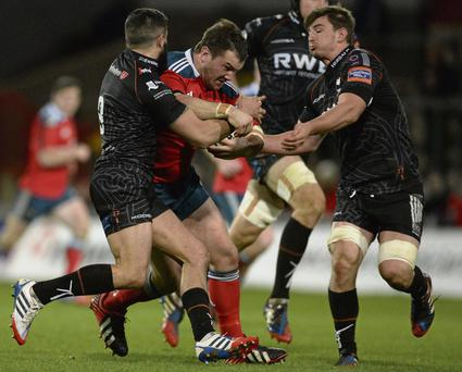 Munster's Damien Varley is tackled by Tito Tebaldi and Sam Lewis during last night's victory over Ospreys. Photo: Diarmuid Greene