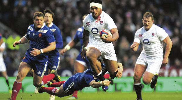 Le Crunch time: France's Morgan Parra tries to get to grips with Manu Tuilagi of England during last year's Six Nations clash at Twickenham. GETTY IMAGE