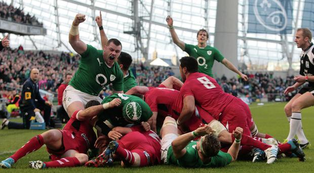 Cian Healy (left) leads the celebrations after Chris Henry's try