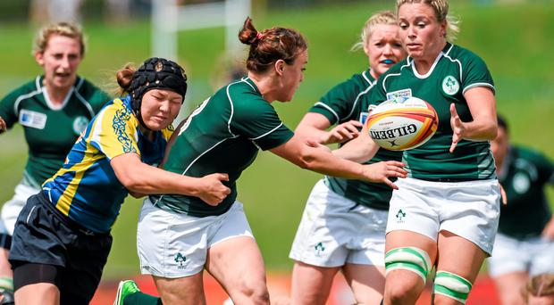 Lynne Cantwell, Ireland, offloads under pressure from Balzhan Koishybayeva, Kazahkstan, to team-mate Sharon Lynch, before going on to score her side's first try.