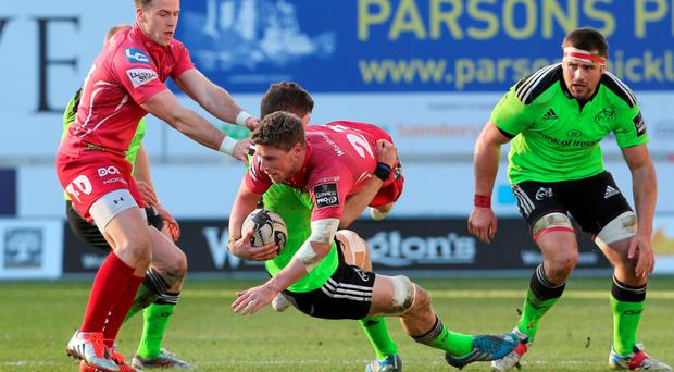 Munster's Jack O'Donoghue tackles Rhys Priestland of Scarlets during the Pro12 game at Parc Y Scarlets in Wales