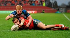 Munster's Simon Zebo scores his side's second try depite the tackle of Darragh Leader