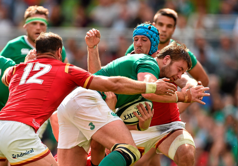 Iain Henderson, Ireland, is tackled by Jamie Roberts, left, and Justin Tipuric, Wales, on his way to scoring his side's first try of the game