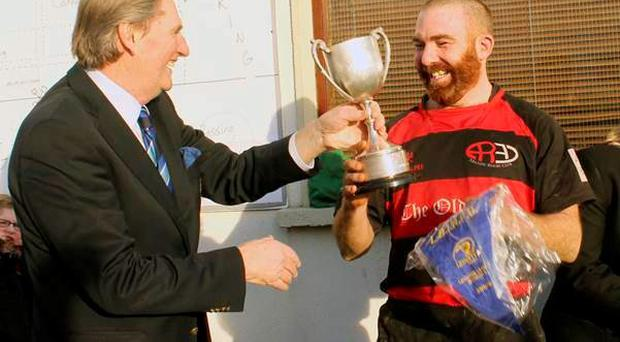 Arklow captain Danny Clear is presented with the Collins Trophy by the former Leinster Branch president Kevin Fitzpatrick