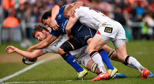 Isa Nacewa is tackled by Iain Henderson and Rory Scholes during yesterday's game at Kingspan Stadium. Photo: Oliver McVeigh