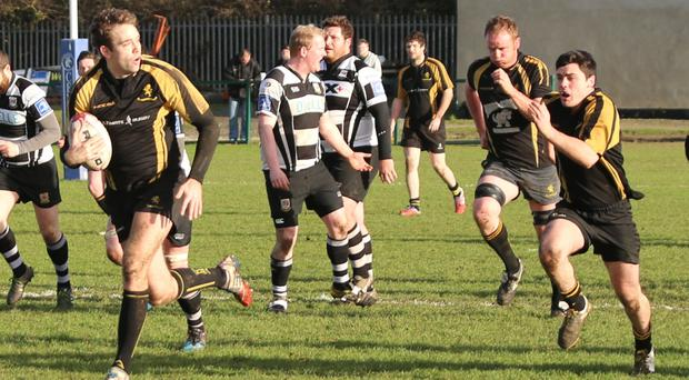 Colin Corkery makes a break for Malahide with Gerry Malarkey in support