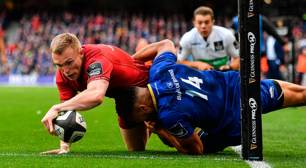 Keith Earls of Munster scores his side's second try despite a last-ditch tackle by Adam Byrne at the Aviva Stadium yesterday. Photo: Brendan Moran/Sportsfile