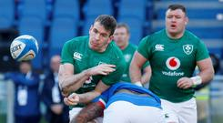 Under pressure: Ireland centre Chris Farrell feels the weight of an Italian tackle in Rome as Dave Kilcoyne (right) looks on. Photo: Reuters
