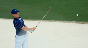 Sand save: Rory McIlroy plays a chip shot out of the bunker at the 10th hole of his opening round. Photo: Getty