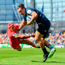 Toulouse's Cheslin Kolbe attempts to tackle Leinster's James Lowe during yesterday's Champions Cup semi-final at the Aviva Stadium. Photo: Ramsey Cardy/Sportsfile