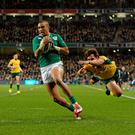 Simon Zebo, Ireland, skips past the tackle of Nick Phipps, Australia, to score his side's first try off the game